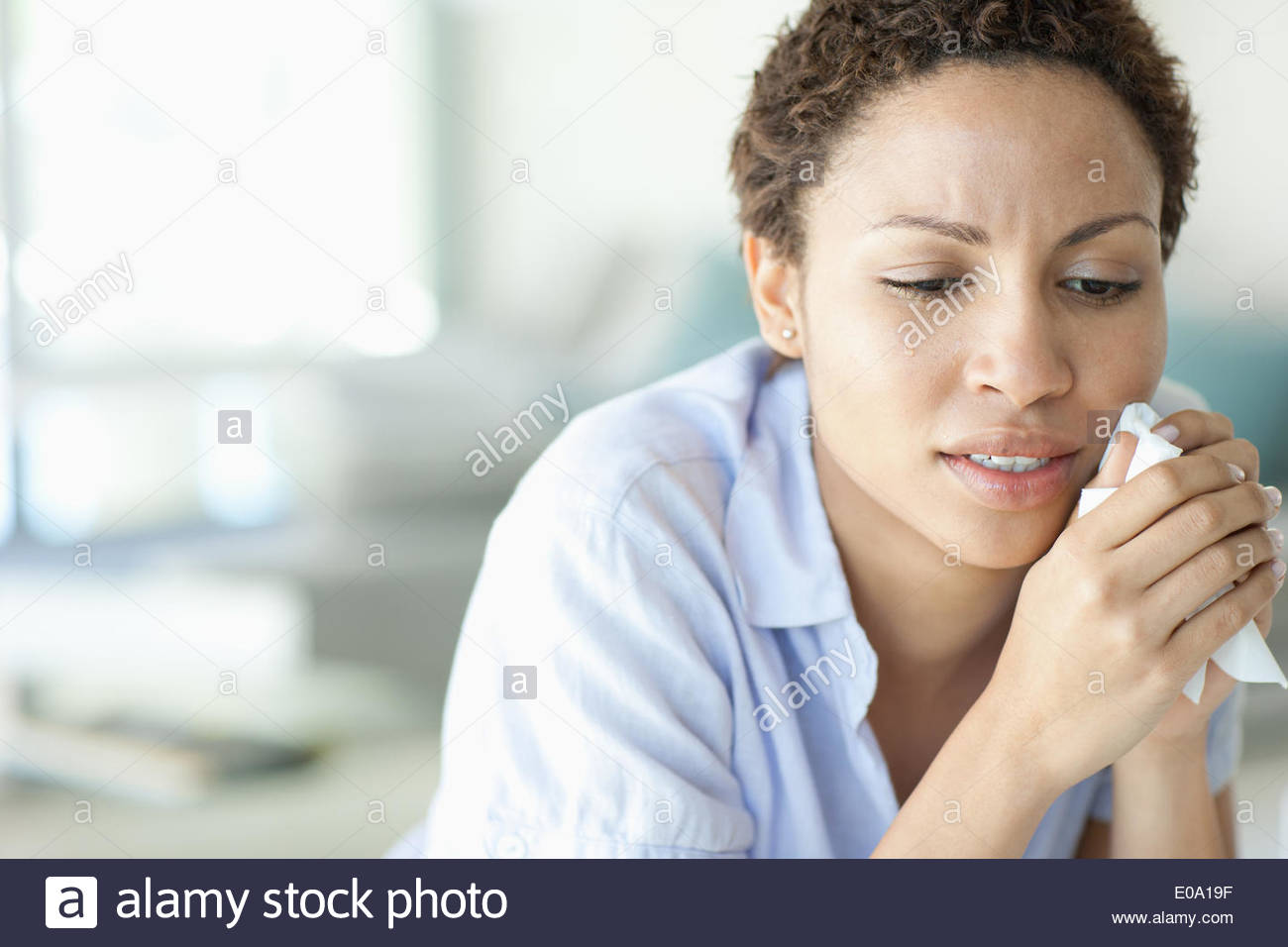 Crying woman holding tissue Photo Stock