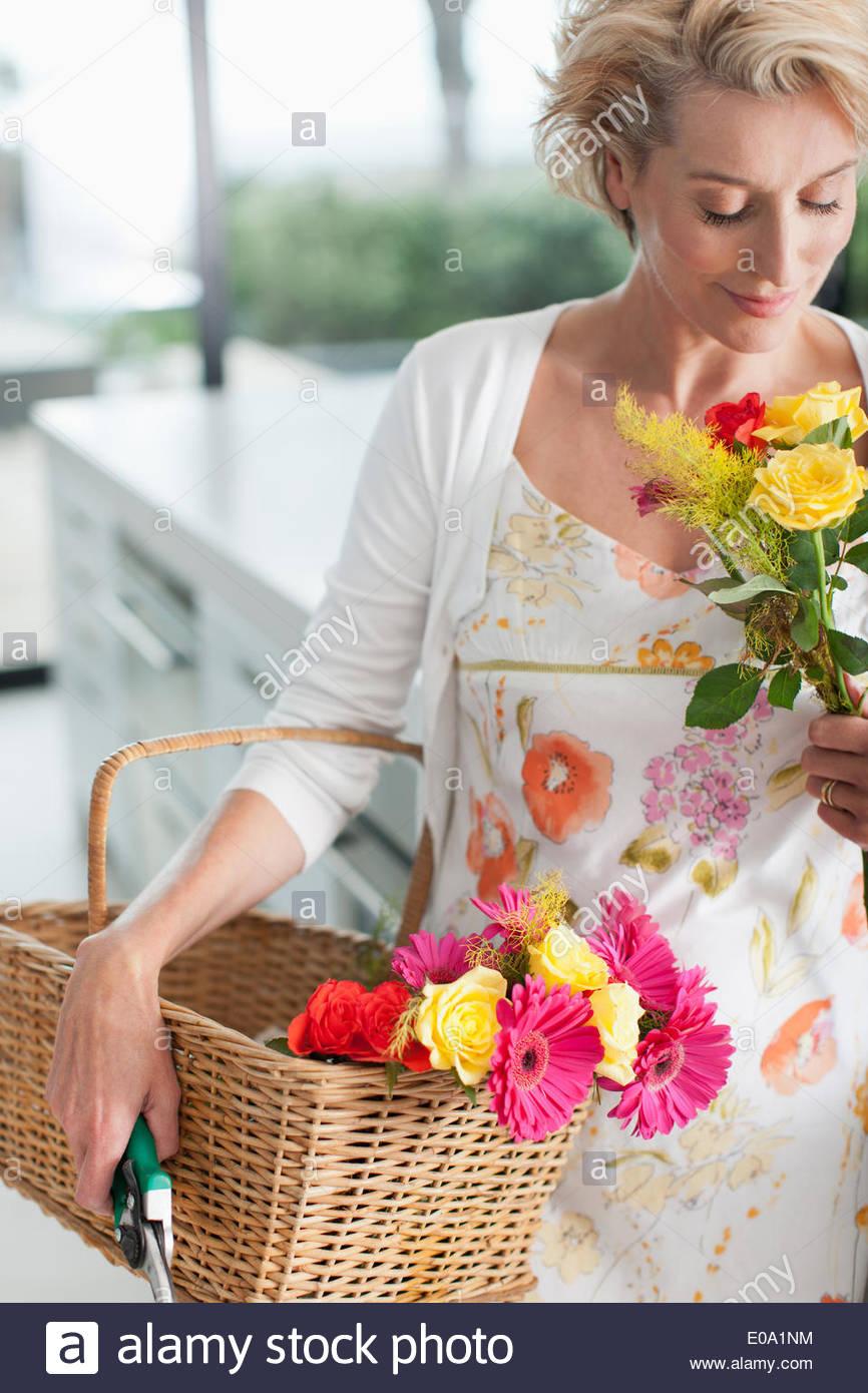 Femme mature avec panier de fleurs Photo Stock