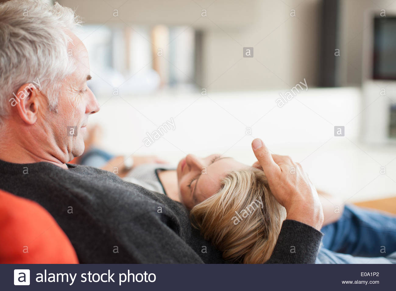 Mature couple laying on couch Photo Stock