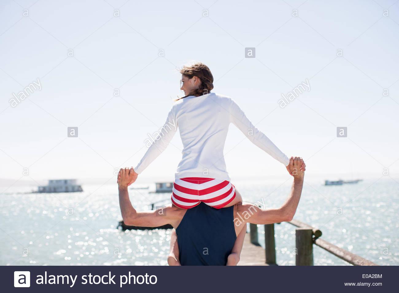 Femme Homme portant sur les épaules sur la jetée à l'ocean Photo Stock