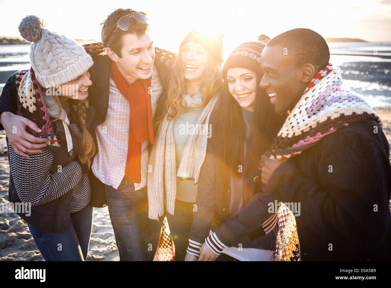 Cinq amis adultes enveloppé dans une couverture sur la plage Photo Stock