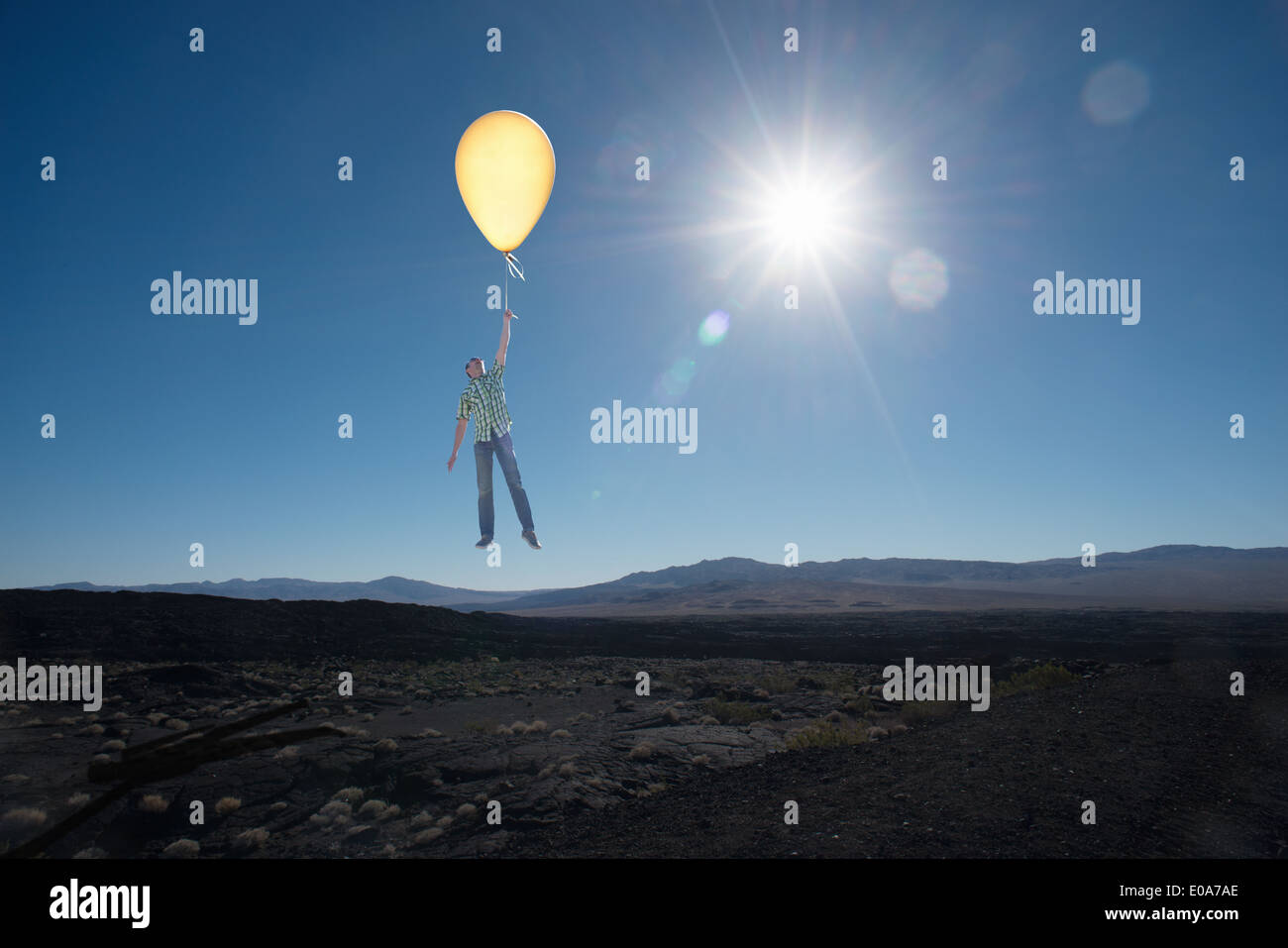 Mid adult man floating avec balloon in desert Photo Stock