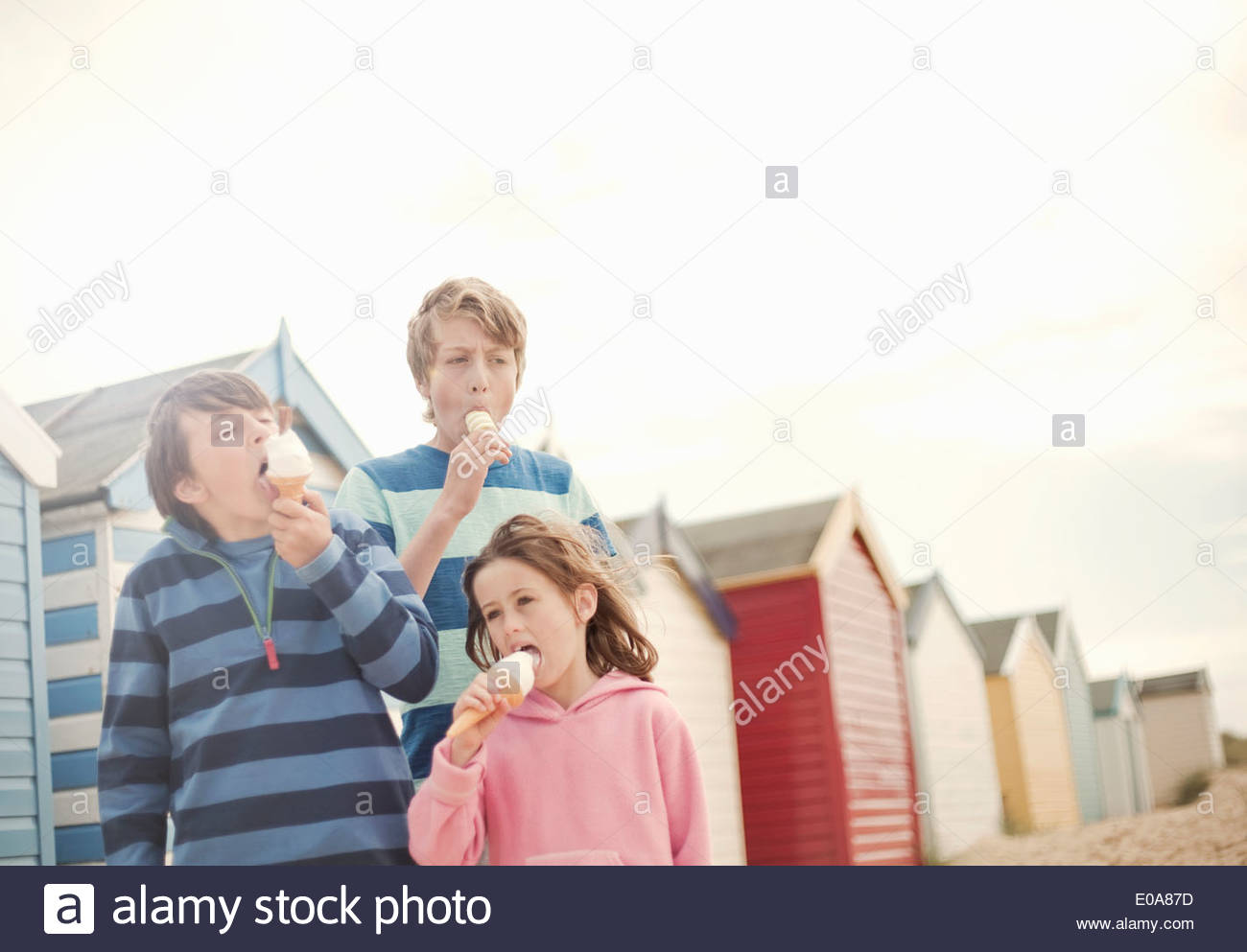Trois enfants à côté des cabines de plage eating ice cream cones, Southwold, Sussex, UK Photo Stock