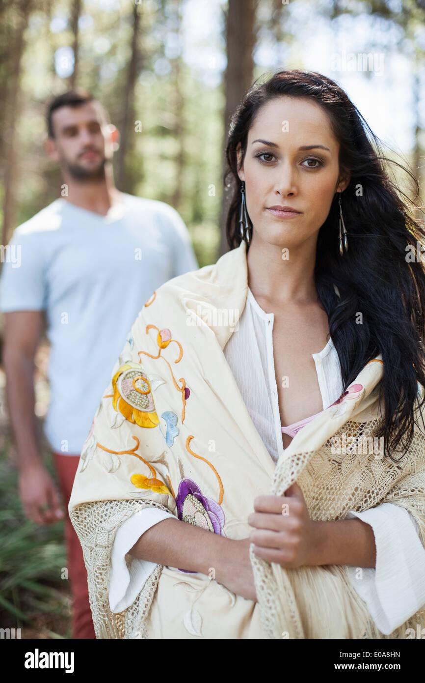 Portrait de jeune femme avec jeune homme derrière elle, en forêt Photo Stock