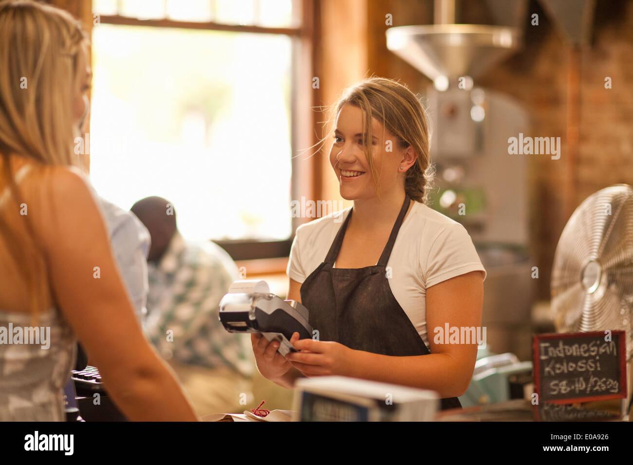 Jeune femme au service client dans un café Photo Stock