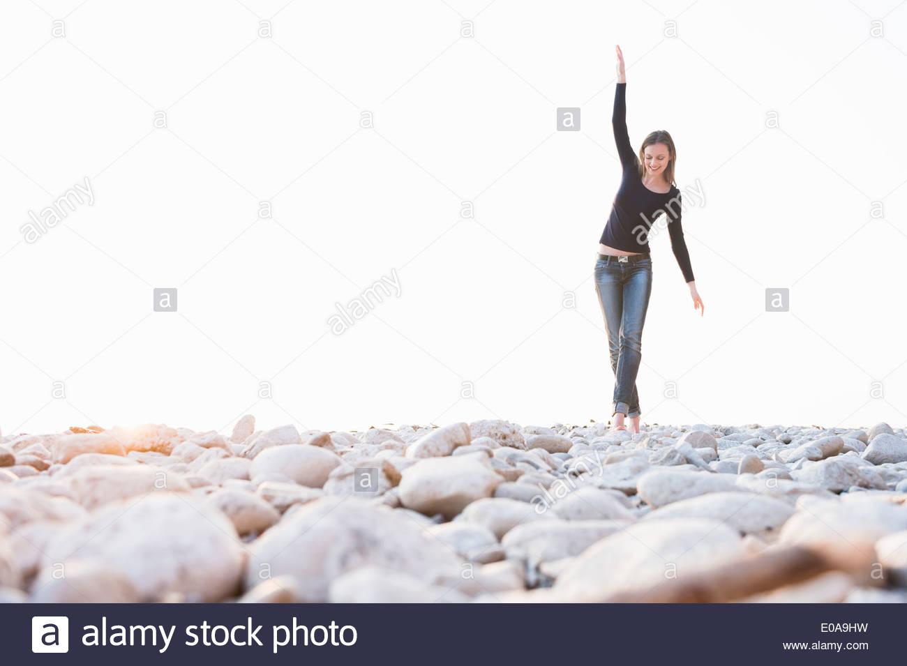 Jeune femme marchant pieds nus sur des pierres à l'autre Photo Stock