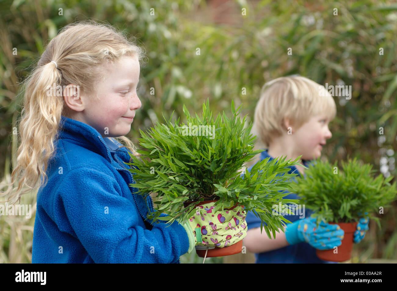 Garçon et fille de l'école avec des plantes dans le jardin Banque D'Images