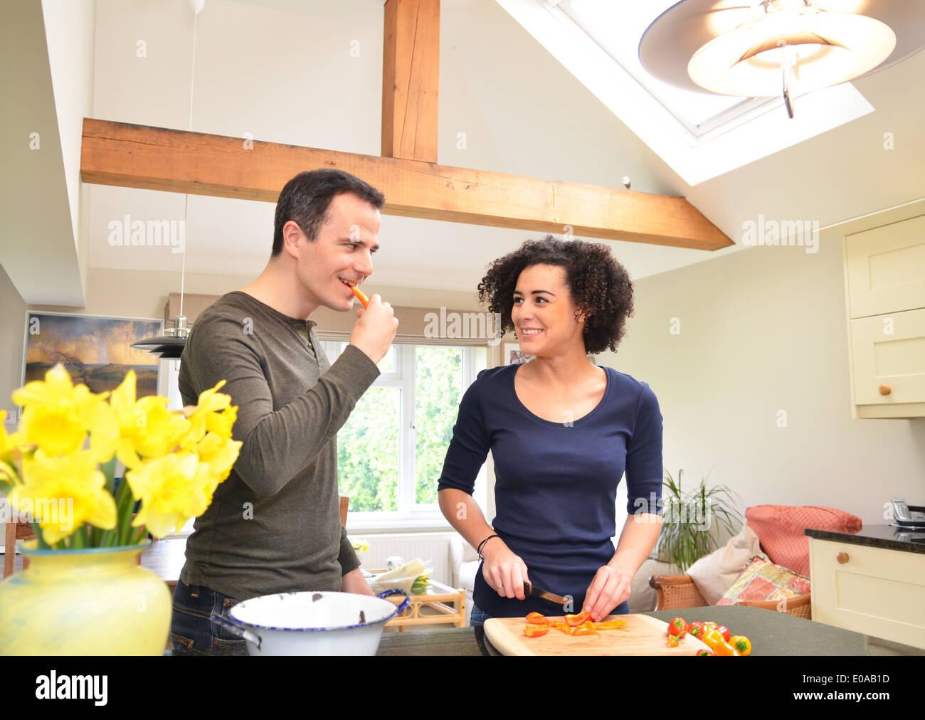 Couple dans la cuisine et dégustation de trancher les poivrons Banque D'Images