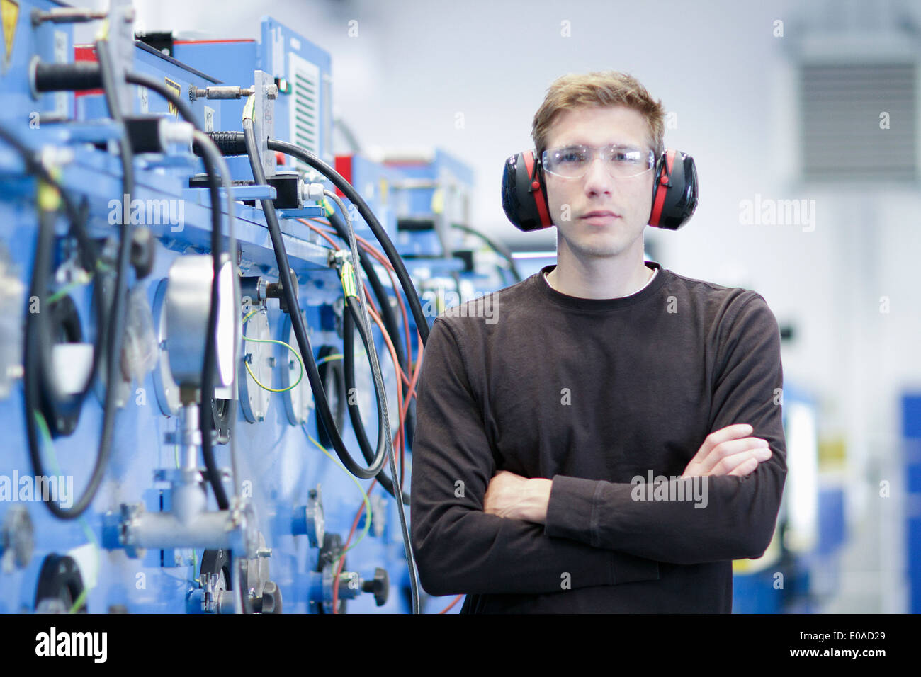Portrait of mid adult male de porter un protège-oreilles en usine d'ingénierie Photo Stock