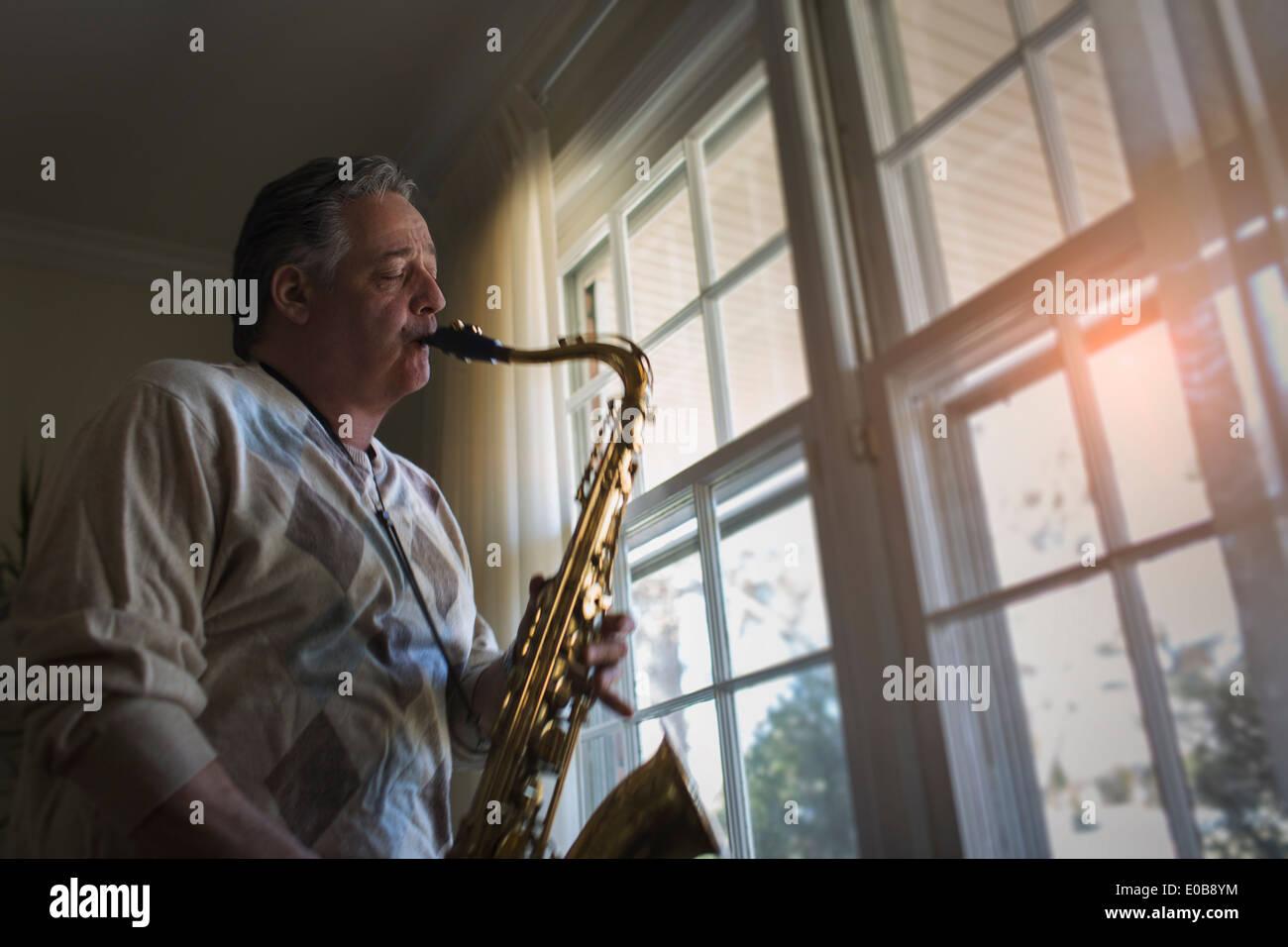Homme mûr à la maison à jouer du saxophone Photo Stock