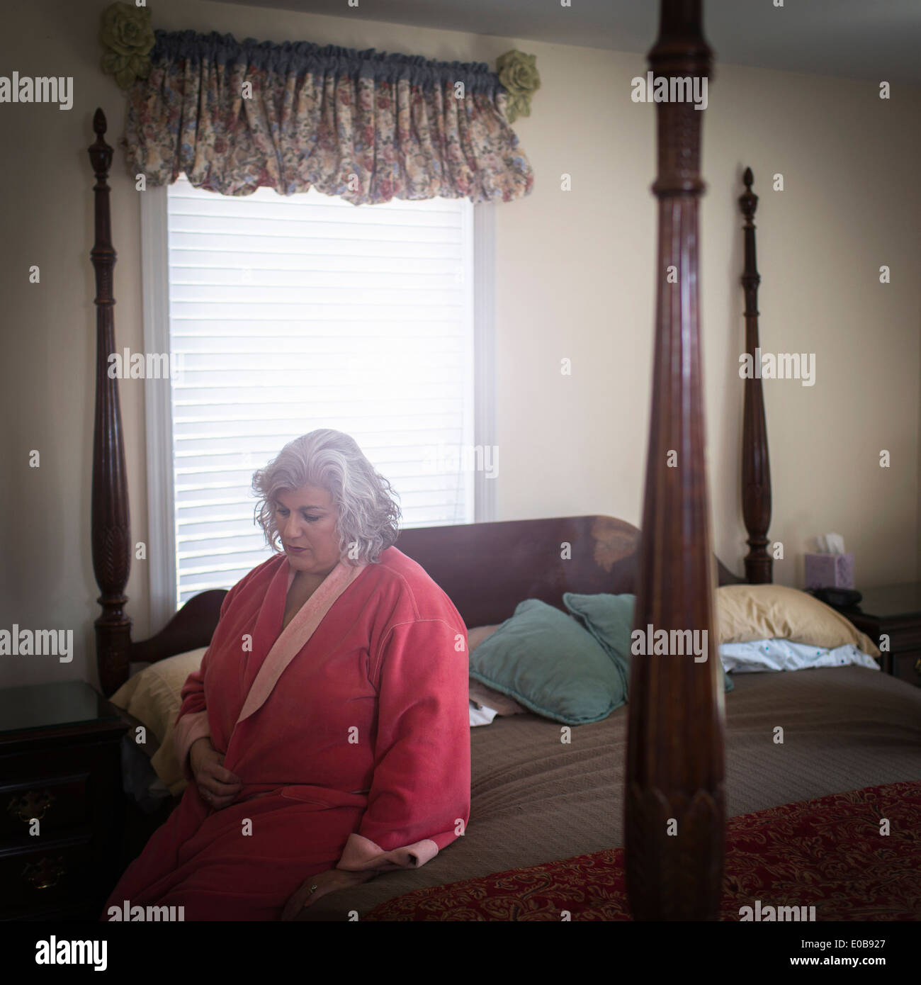 Malheureux mature woman sitting on bed Photo Stock