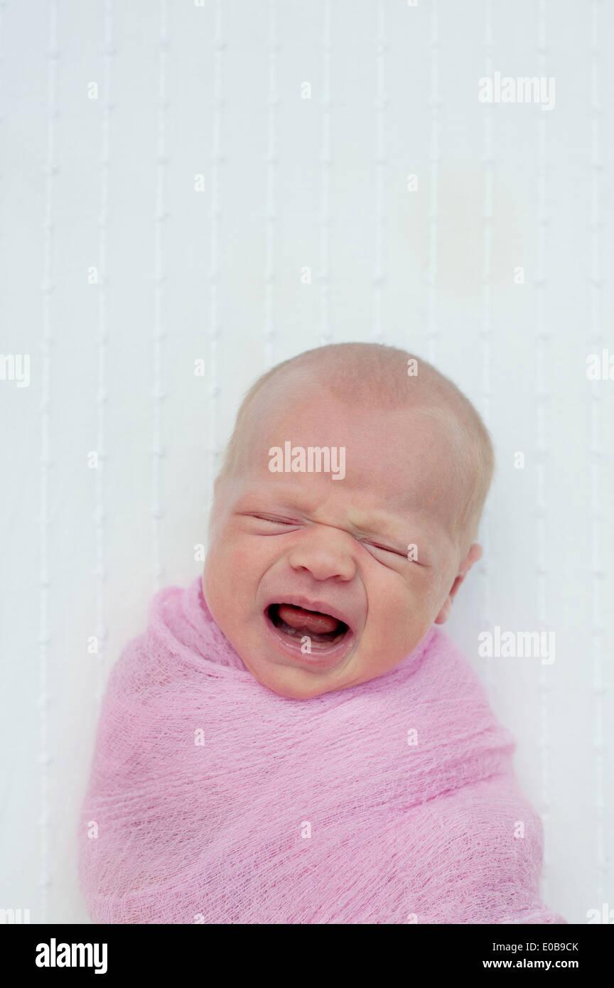 Les pleurs de bébé, enveloppé dans une couverture Photo Stock