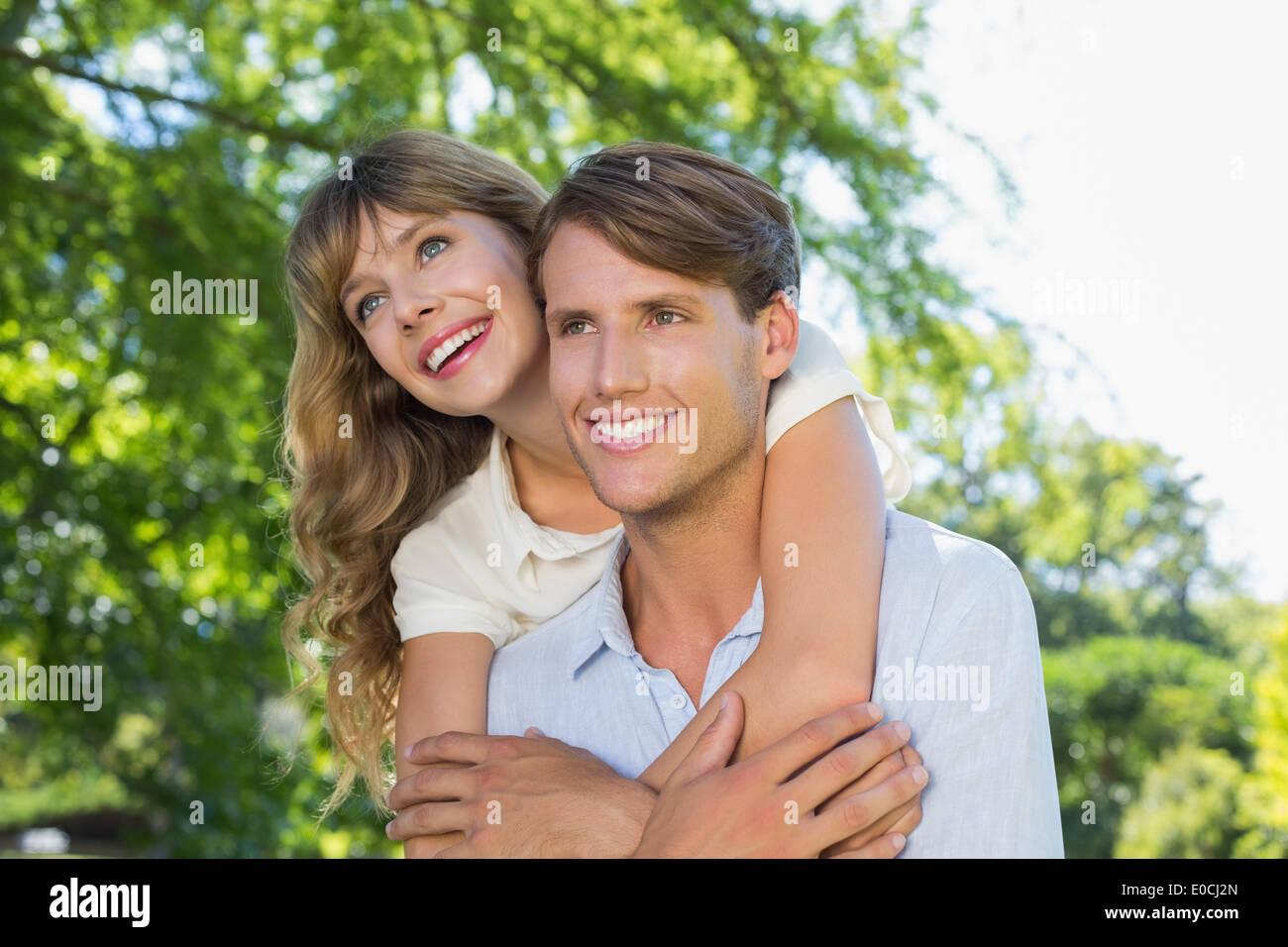 Homme donnant à sa jolie petite amie une piggy back in the park smiling Photo Stock