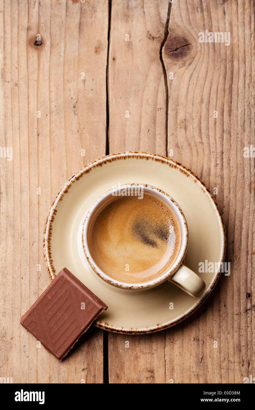 Tasse de café avec du chocolat sur fond de bois Photo Stock