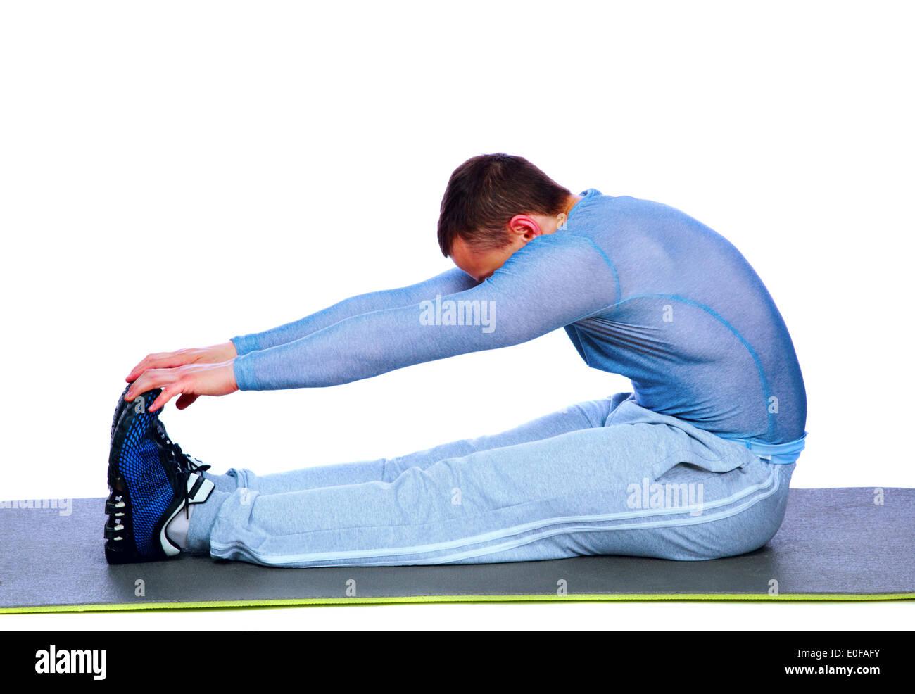Homme assis de remise en forme et de faire des exercices d'étirement sur fond blanc Photo Stock