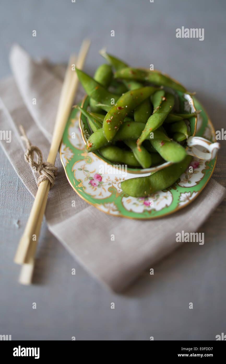 Tasse de thé de chili edamame avec baguettes Photo Stock