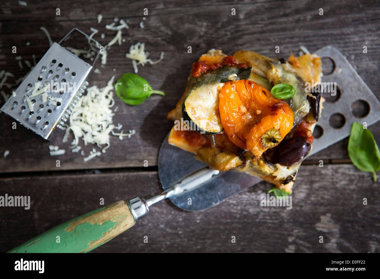 Une tranche de pizza maison avec du poivre, courgette, olive et basilic et d'une râpe à fromage Photo Stock