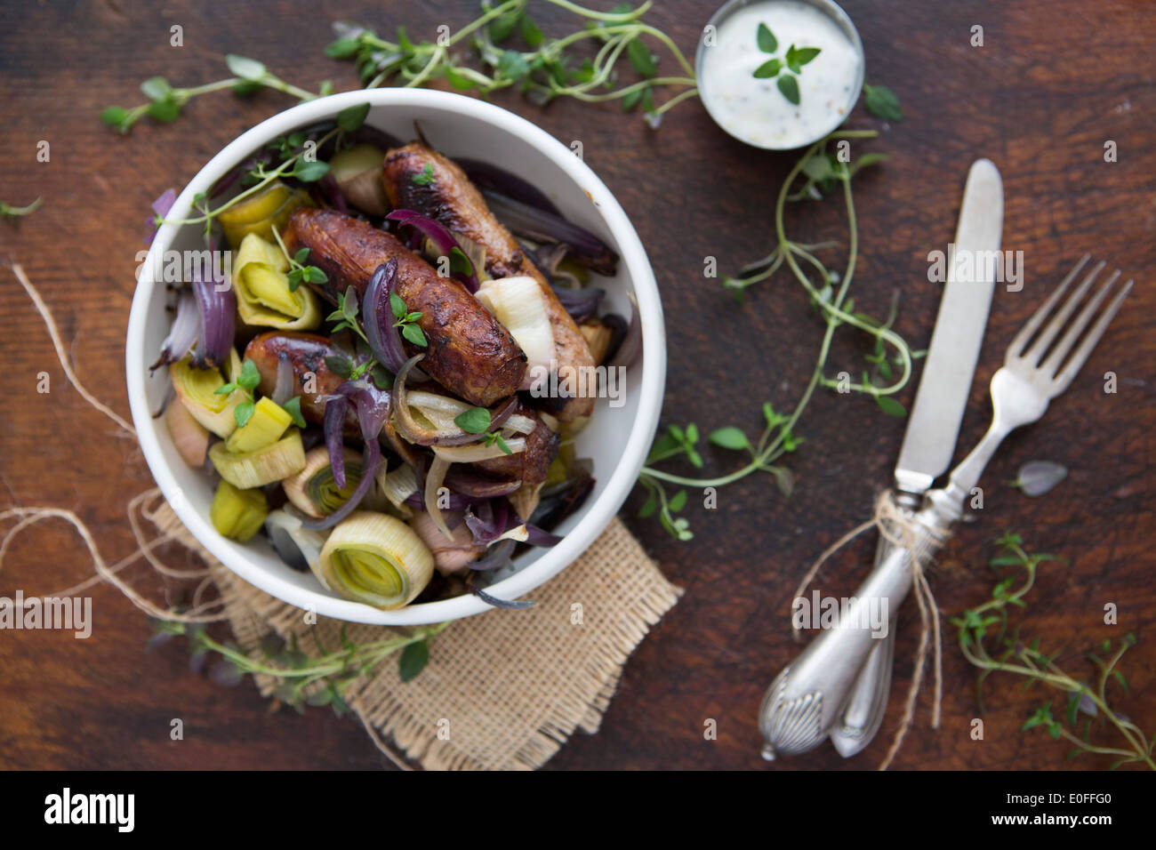 Saucisse, le poireau, l'oignon rouge et le thym dans un bol avec de la crème Banque D'Images