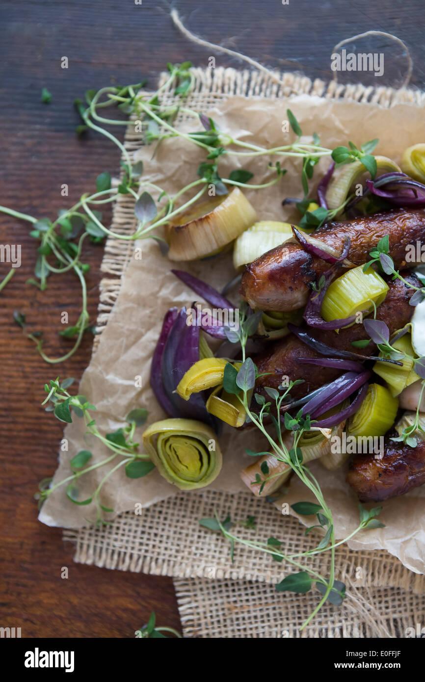 Saucisse, le poireau, l'oignon rouge et le thym sur le papier parchemin Banque D'Images