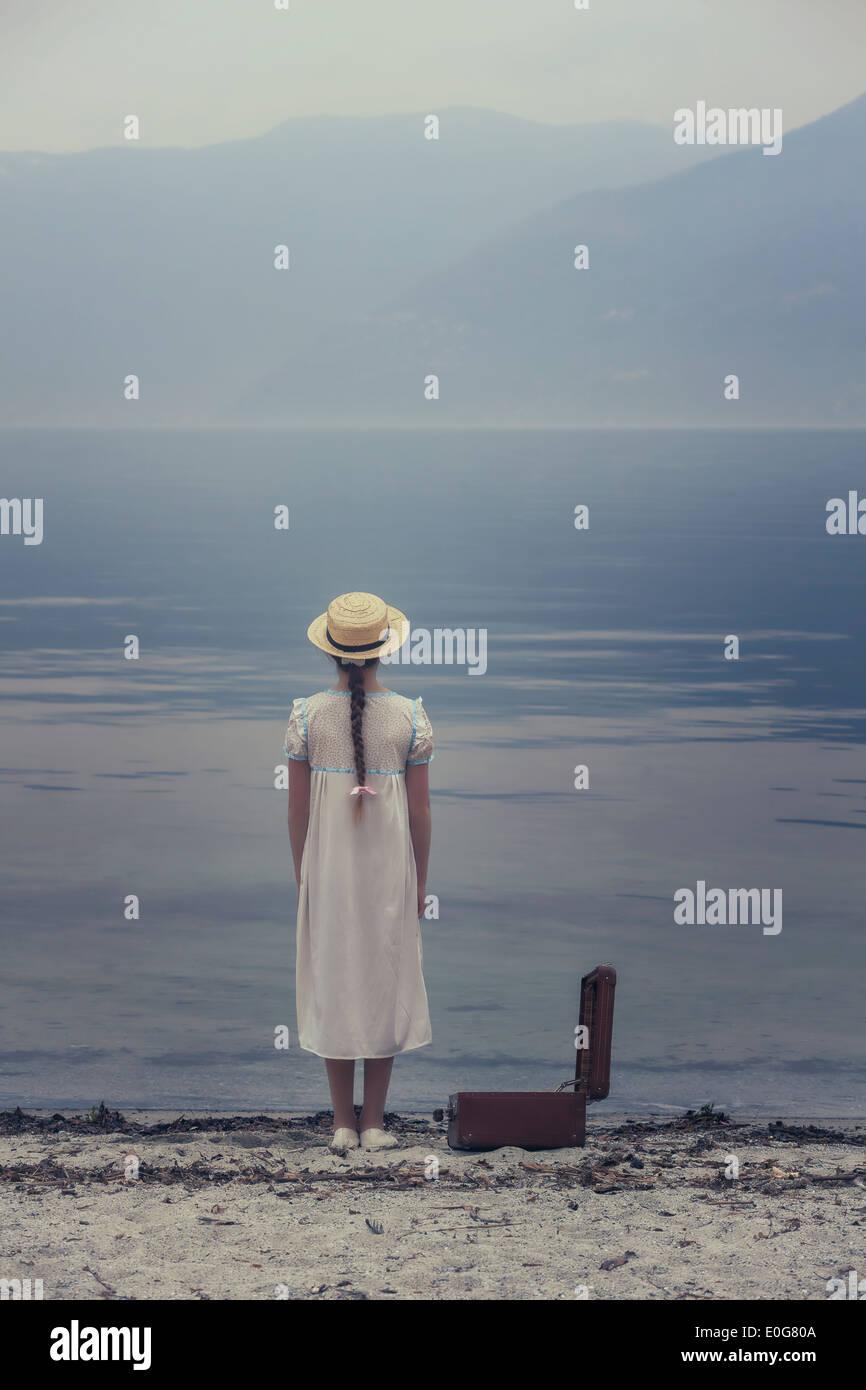 Une fille à un lac avec une valise ouverte Photo Stock