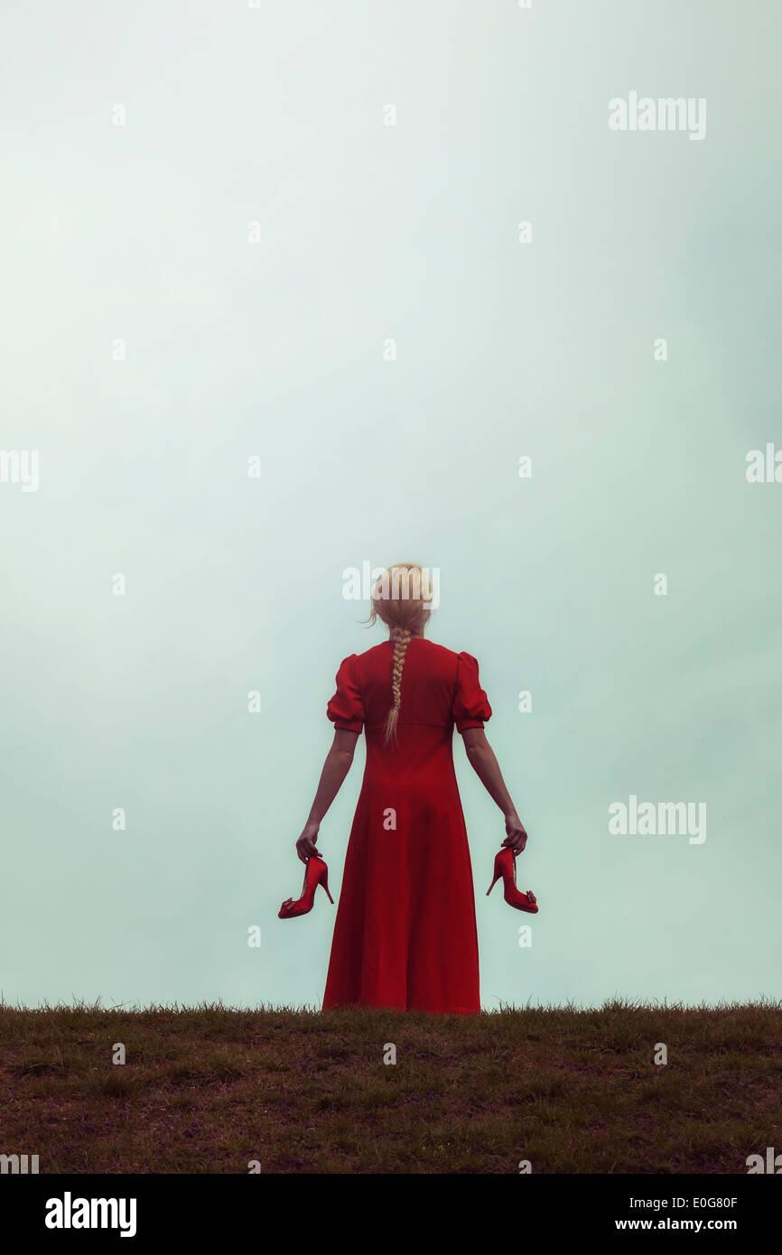 Une fille dans une robe rouge sur un pré avec ses chaussures dans ses mains Photo Stock
