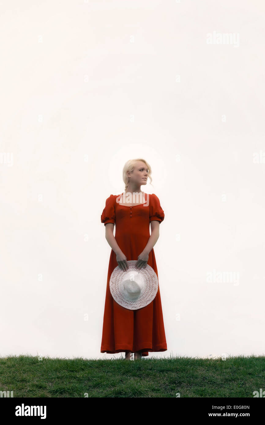 Une femme dans une robe rouge avec un chapeau blanc Photo Stock