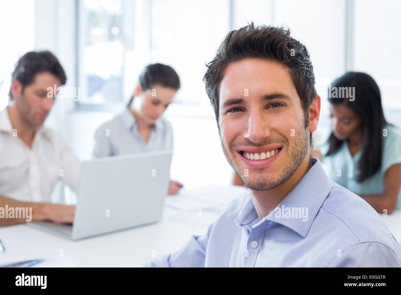 Attractive businessman smiling en milieu de travail Photo Stock