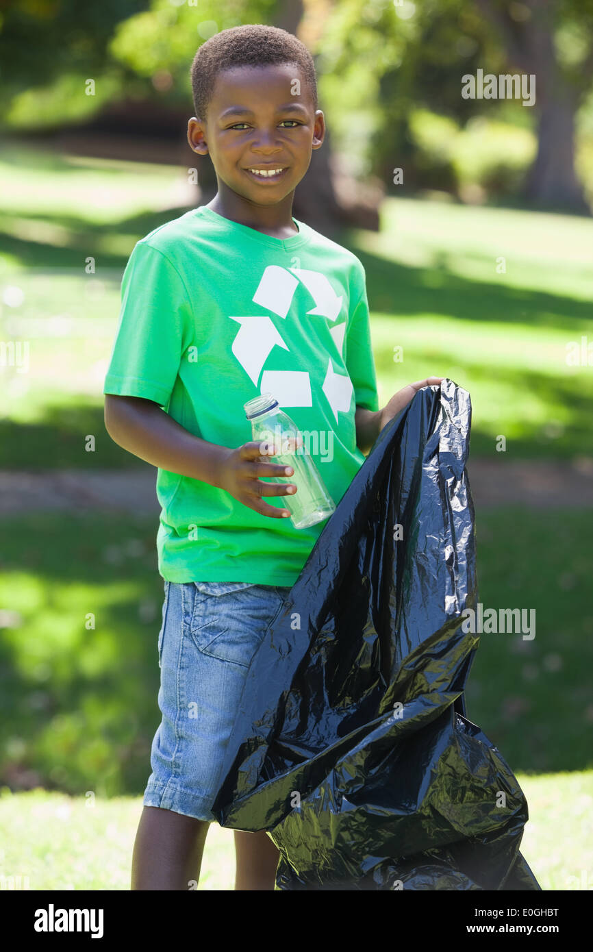 Jeune garçon dans le recyclage tshirt picking up trash Photo Stock