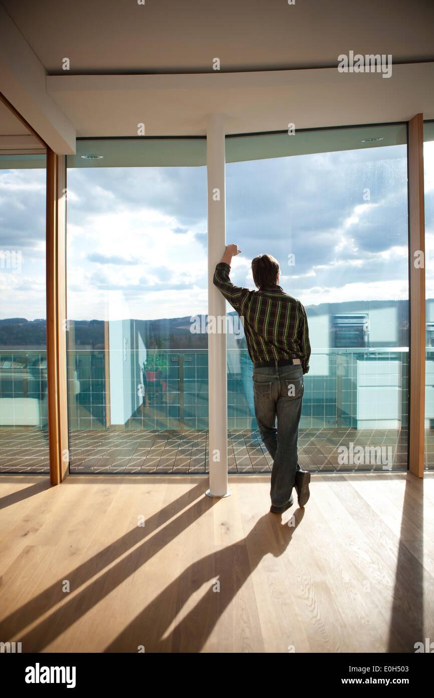 Homme regardant dans le ciel à travers la fenêtre maison passive, Styrie, Autriche Photo Stock