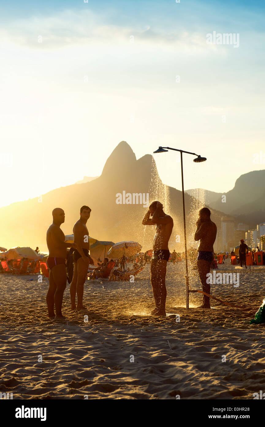RIO DE JANEIRO, Brésil - le 25 janvier 2014: Groupe d'hommes brésilien se tenir sous les douches en plein air sur la plage d'Ipanema au coucher du soleil. Photo Stock