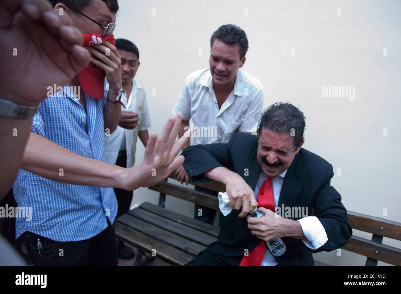 Tegucigalpa, Honduras. 13 mai, 2014. L'ex-Président du Honduras Manuel Zelaya (R) réagit après touchés par les gaz lacrymogènes et d'être évacué avec ses partisans du Congrès national, à Tegucigalpa, Honduras, le 13 mai 2014. Partisans et des députés du Parti de la refondation et de la Liberté (Libre, pour son sigle en espagnol), la seconde force politique au Honduras, a éclaté dans le Congrès national le mardi, après des affrontements avec des éléments de la police qui gardait le Palais législatif. Credit: Rafael Ochoa/Xinhua/Alamy Live News Banque D'Images