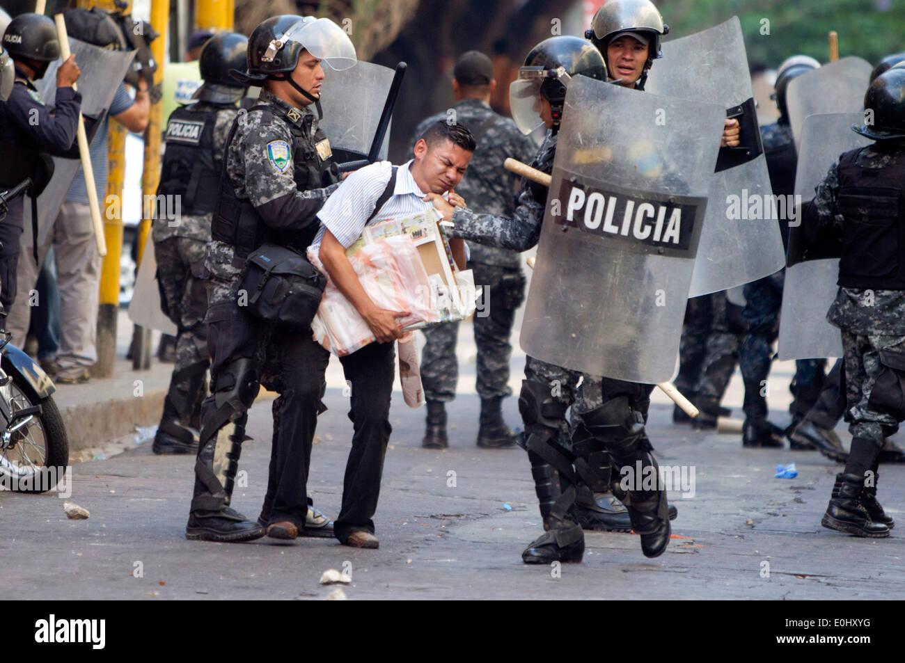 Tegucigalpa, Honduras. 13 mai, 2014. Des éléments de la police de détenir une personne au cours d'un affrontement entre partisans de l'ex-Président du Honduras, Manuel Zelaya, et la police, devant le Congrès national à Tegucigalpa, Honduras, le 13 mai 2014. Partisans et des députés du Parti de la refondation et de la Liberté (Libre, pour son sigle en espagnol), la seconde force politique au Honduras, a éclaté dans le Congrès national le mardi, après des affrontements avec des éléments de la police qui gardait le Palais législatif. Credit: Rafael Ochoa/Xinhua/Alamy Live News Banque D'Images