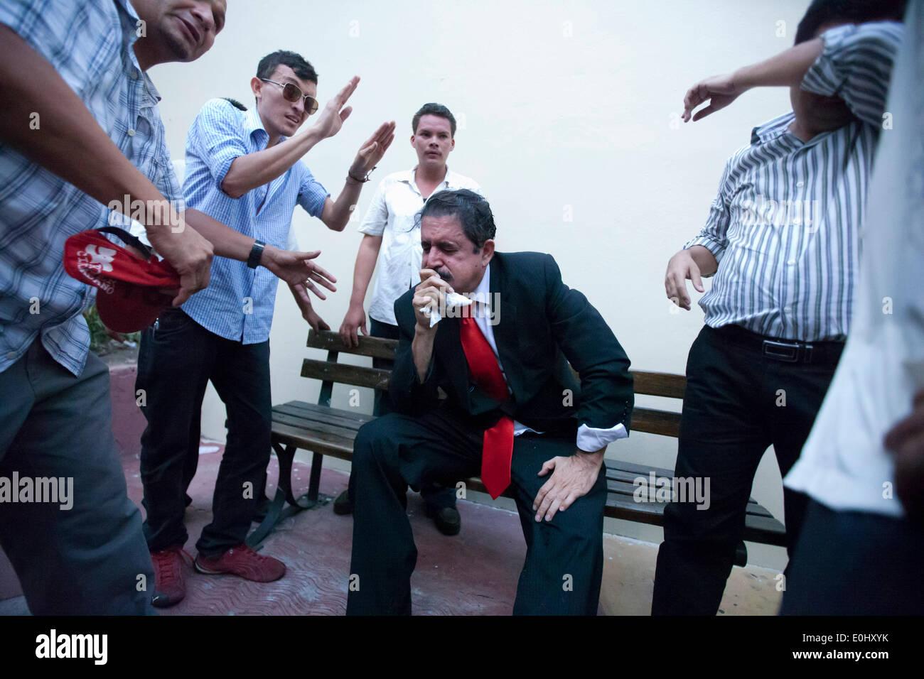 Tegucigalpa, Honduras. 13 mai, 2014. L'ex-Président du Honduras Manuel Zelaya (C) porte sur sa face de gaz lacrymogènes, après avoir été évacuée avec ses partisans du Congrès national, à Tegucigalpa, Honduras, le 13 mai 2014. Partisans et des députés du Parti de la refondation et de la Liberté (Libre, pour son sigle en espagnol), la seconde force politique au Honduras, a éclaté dans le Congrès national le mardi, après des affrontements avec des éléments de la police qui gardait le Palais législatif. Credit: Rafael Ochoa/Xinhua/Alamy Live News Banque D'Images