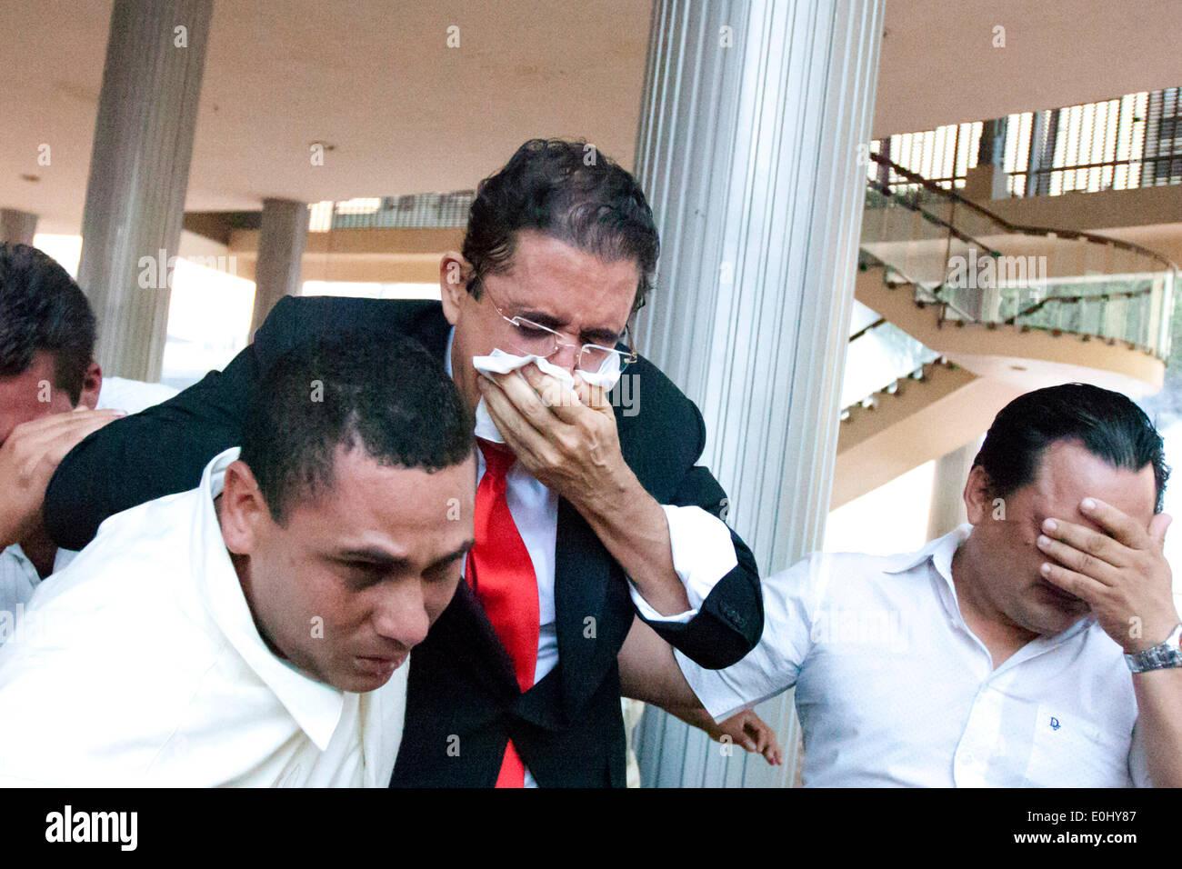 Tegucigalpa, Honduras. 13 mai, 2014. L'ex-Président du Honduras Manuel Zelaya (C) c'est son visage de gaz lacrymogène après avoir été évacuée avec ses partisans du Congrès national, à Tegucigalpa, Honduras, le 13 mai 2014. Partisans et des députés du Parti de la refondation et de la Liberté (Libre, pour son sigle en espagnol), la seconde force politique au Honduras, a éclaté dans le Congrès national le mardi, après des affrontements avec des éléments de la police qui gardait le Palais législatif. Credit: Rafael Ochoa/Xinhua/Alamy Live News Banque D'Images