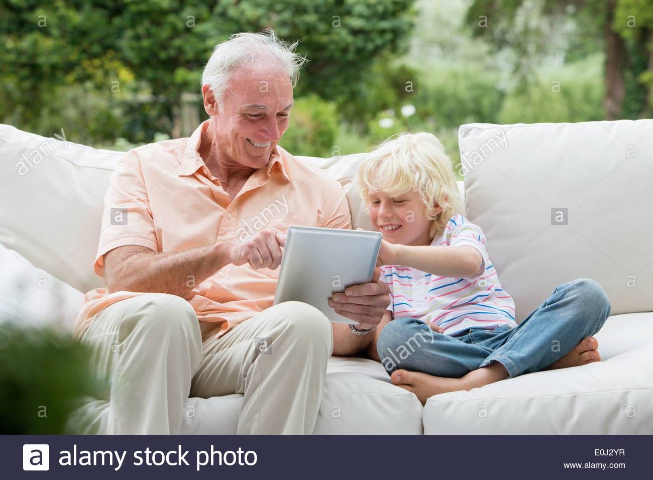 Grand-père et petit-fils using digital tablet on outdoor sofa Photo Stock