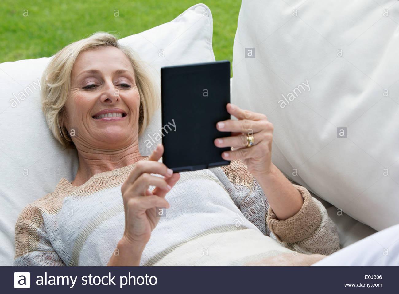 Senior woman laying on sofa d'extérieur et using digital tablet Photo Stock