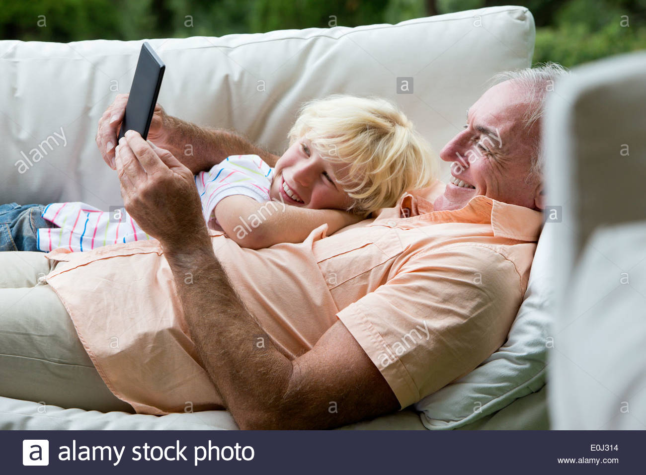 Smiling grandfather and grandson portant sur canapé outdoor with digital tablet Photo Stock