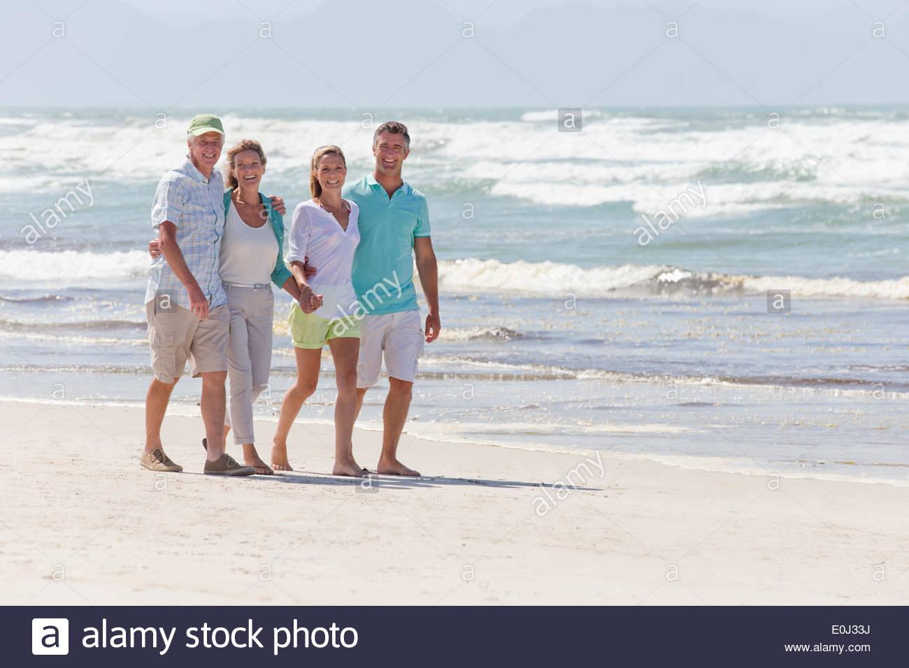 Portrait of happy couples walking on sunny beach Photo Stock