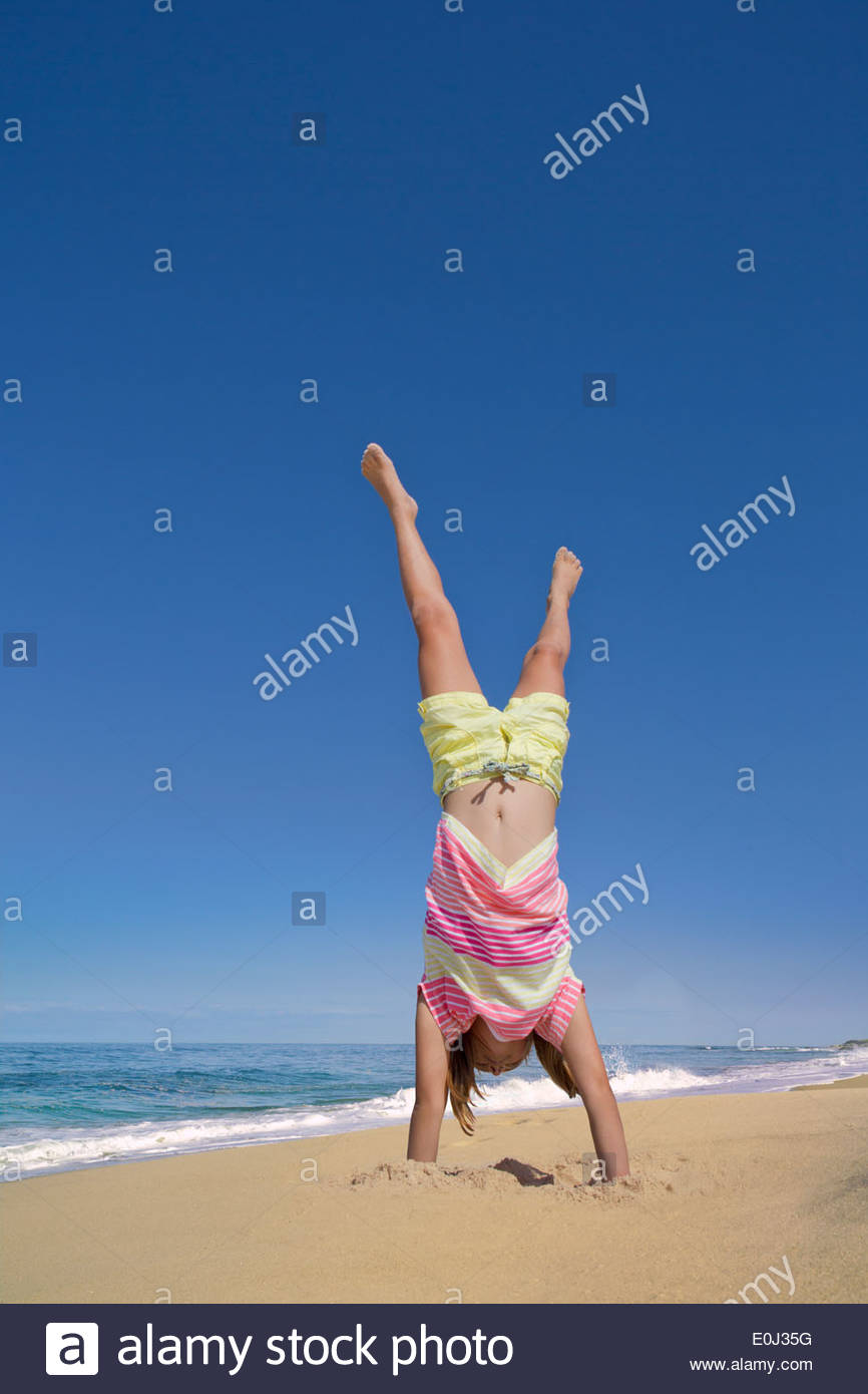 Girl doing handstand on sunny beach Photo Stock