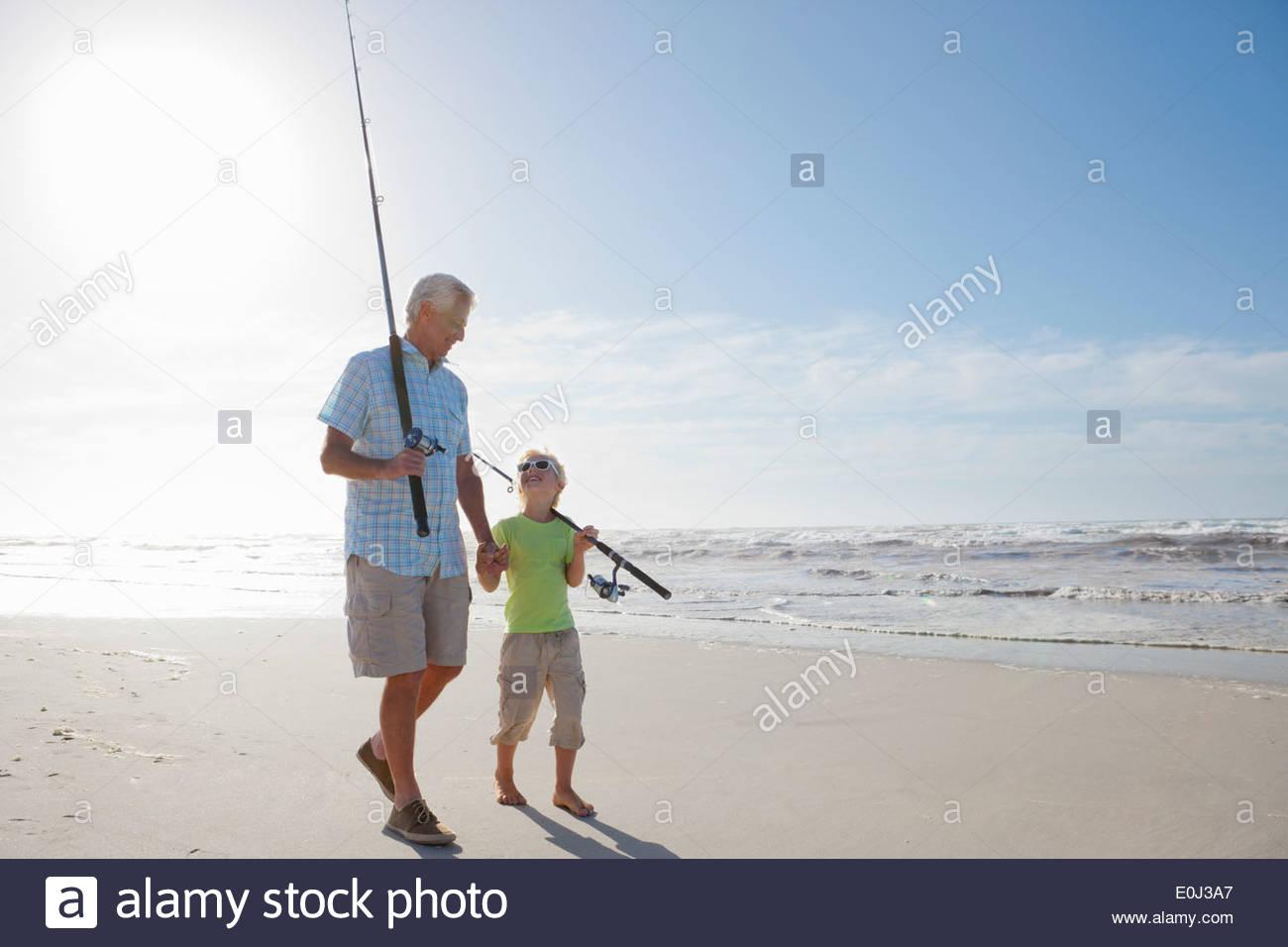 Grand-père et petit-fils avec des cannes à pêche sur sunny beach Photo Stock