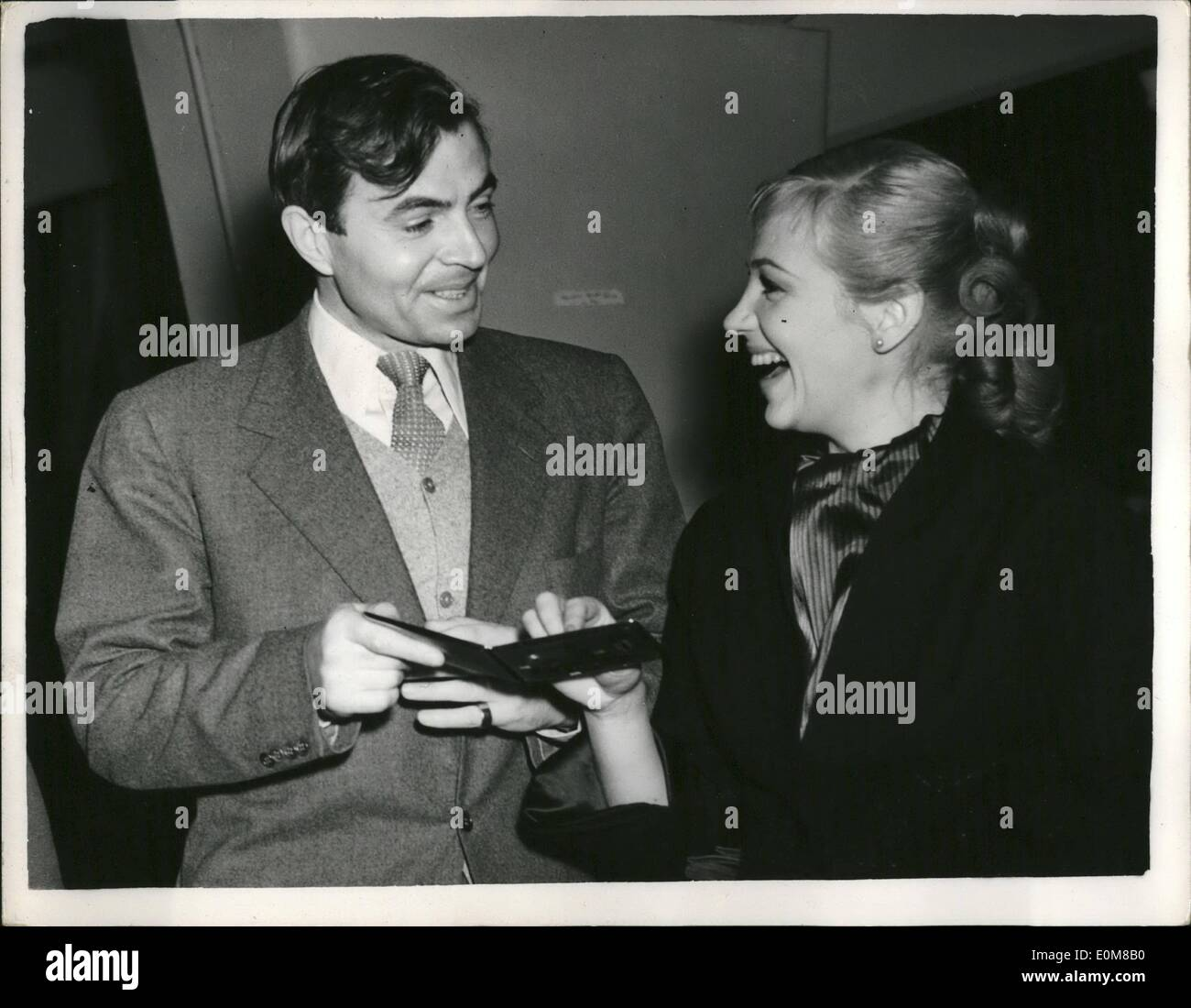 Le 12 décembre 1953 - Ouverture du nouveau Stagesat Shepperton trois nouveaux stades, entièrement équipée et la formation d'indépendants avec la vinaigrette et composent, ont inauguré aujourd'hui par Mlle Margaret Leighton à Shepperton, qui devient maintenant le plus grand, plus moderne studio de travail au Royaume-Uni montre Photo: James Mason propose Hildegaard Neff, la star du cinéma allemand, une cigarette à l'ouverture aujourd'hui. Ils sont en partie dans le film ''Berlin'', qui sont réalisés à l'Shepperton studios. Photo Stock