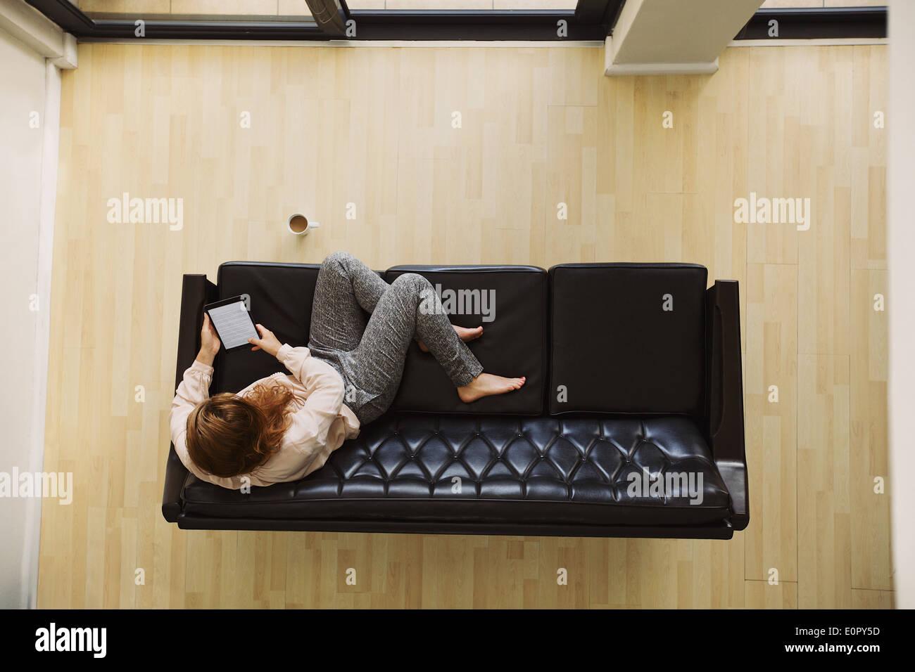 Vue de dessus de jeune femme assise sur une table à l'aide de la tablette numérique. Female relaxing on sofa avec un e-reader dans son appartement. Banque D'Images