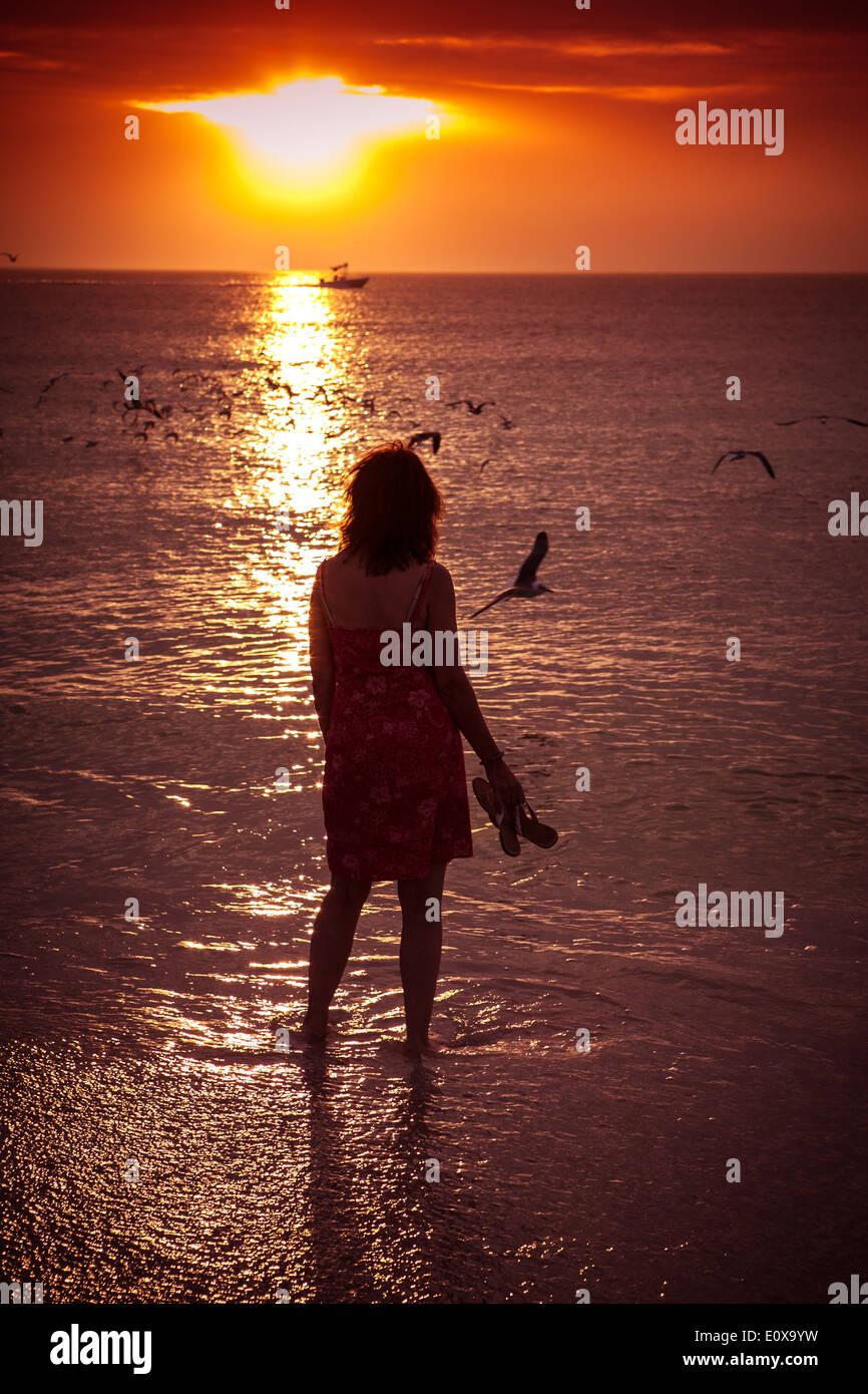 Femme seule sur une plage au coucher du soleil Photo Stock