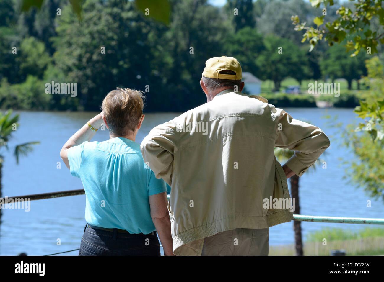 Les retraités / retraités, senior couple resting et passent à côté d'un lac dans un parc Photo Stock