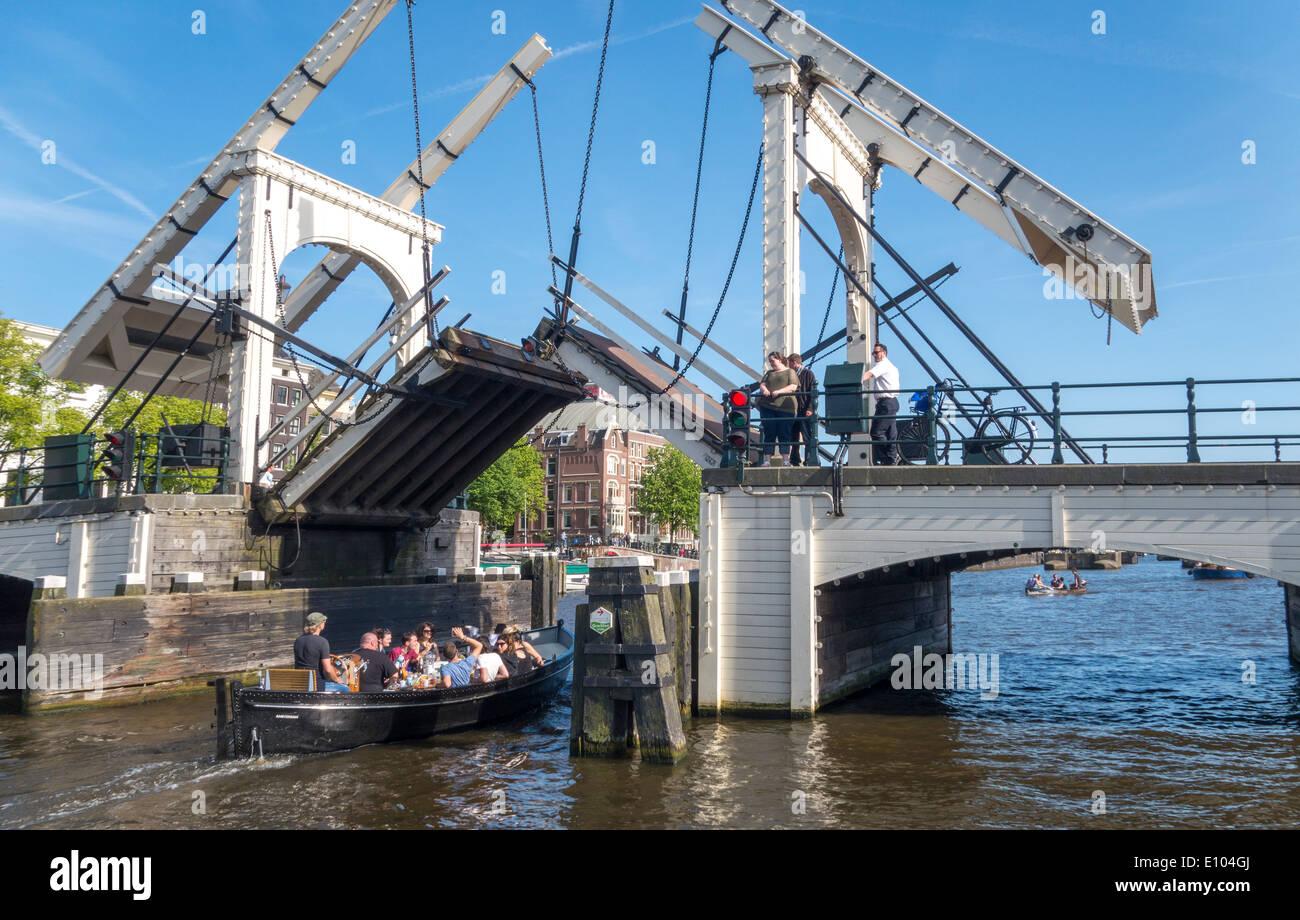 Amsterdam Magere Brug, Skinny Bridge, petit bateau passant du pont-levis. Un bridgeman sur vélo est la fermeture du pont basculant. Banque D'Images