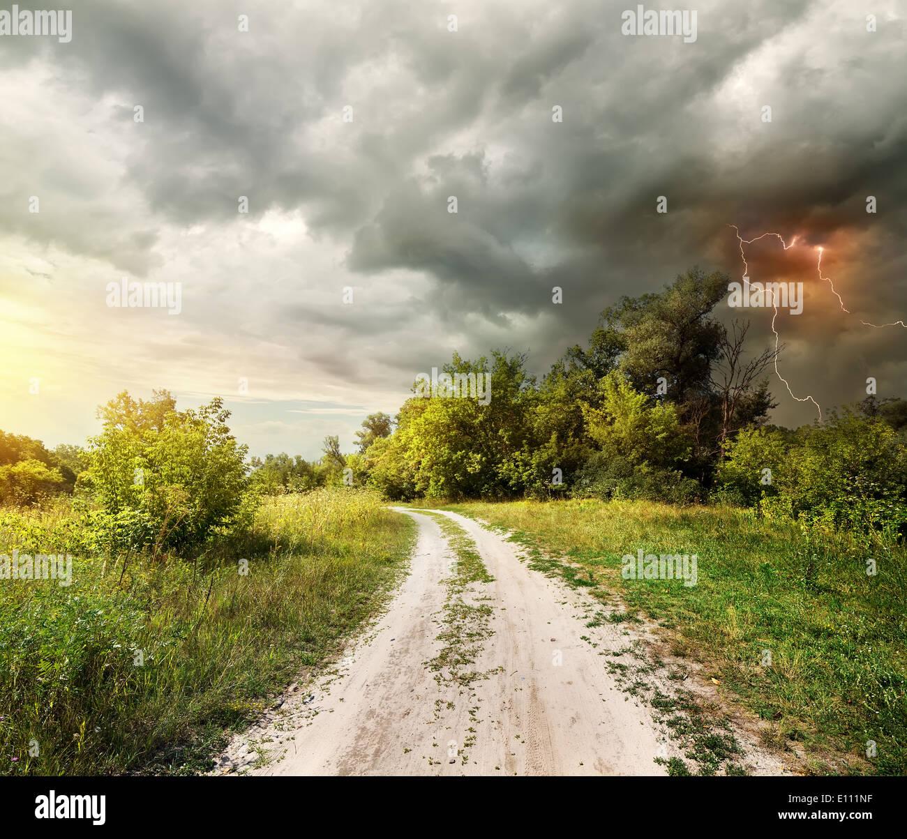Route de campagne à travers la forêt et la foudre Photo Stock