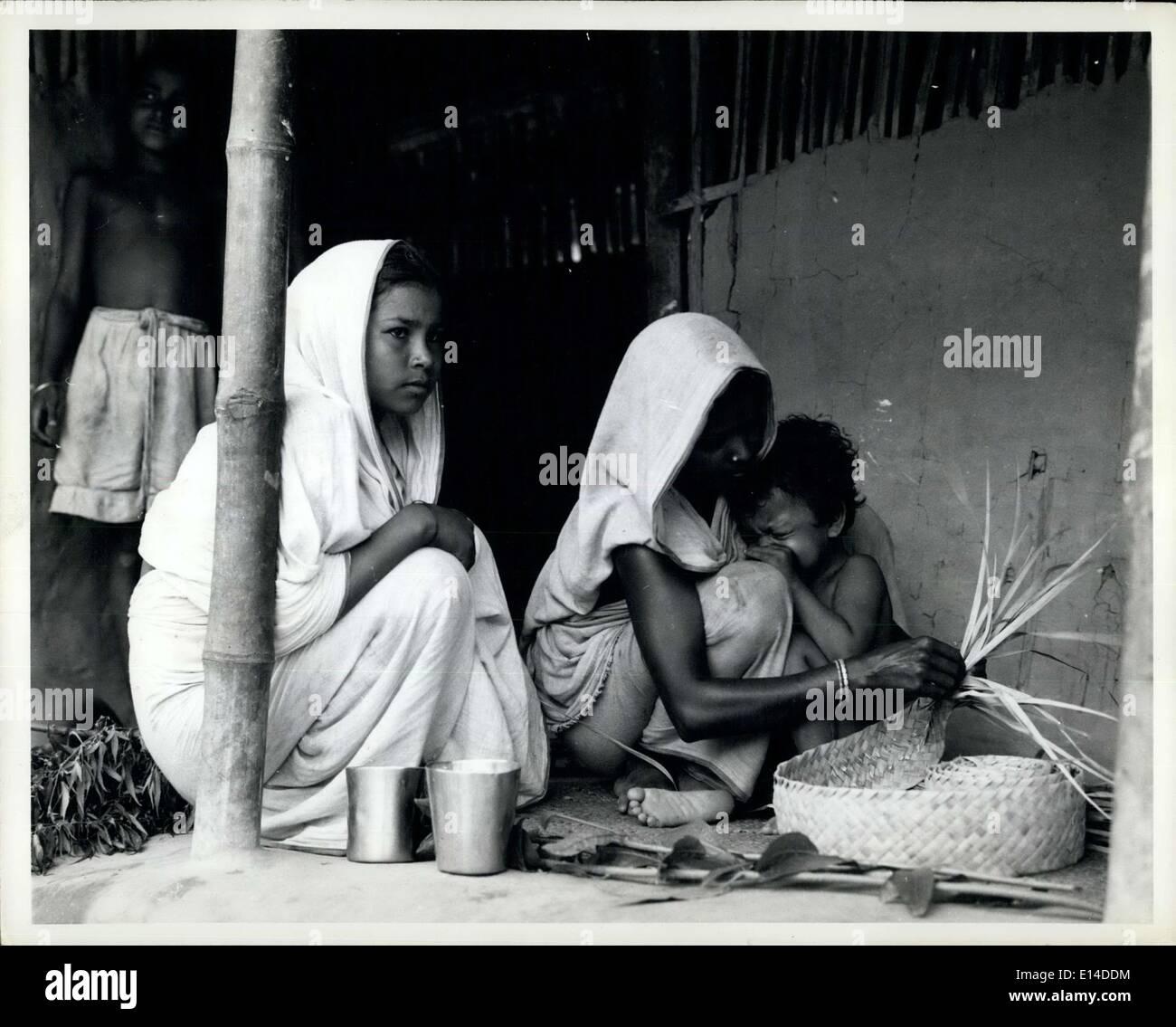 Le 17 avril 2012 - Pakistan élargit son programme de développement des collectivités: Pour aider le gouvernement du Pakistan dans l'expansion de son programme pour aider à résoudre les problèmes sociaux, l'Organisation des Nations unies pour l'enfance (UNICEF) fournit des experts, du matériel et des fournitures pour le gouvernement pour les projets de développement communautaire. Jeune mère pakistanaise continue calmement le tissage des tapis de feuilles de palme qu'elle la réconforte bébé qui pleure. Ils sont parmi les nombreuses qui bénéficient de projets de développement communautaire institué par le gouvernement du Pakistan. Photo Stock