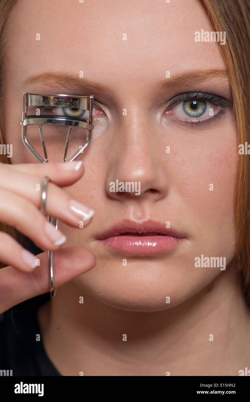 Girl using eyelash curlers Photo Stock