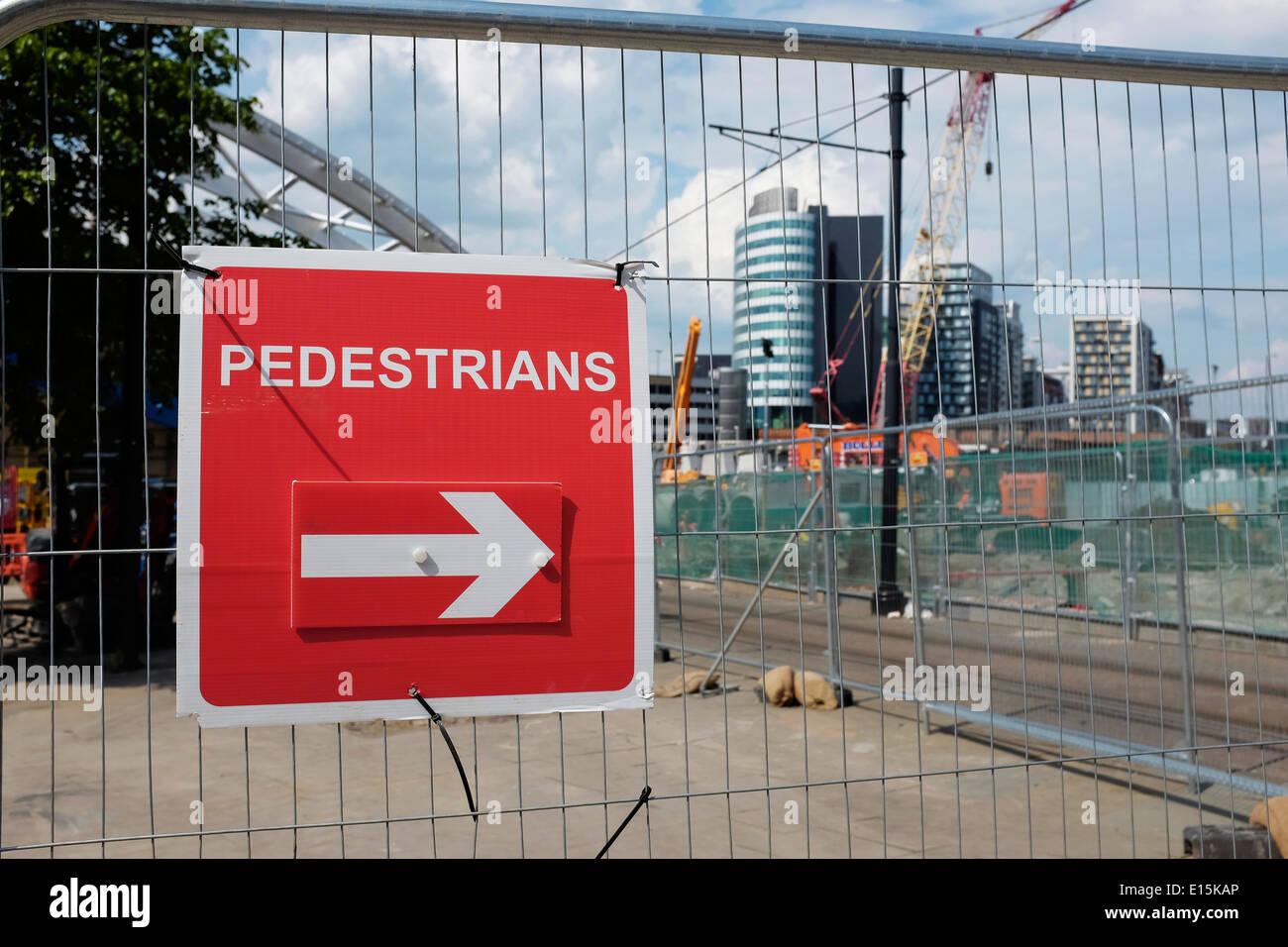Inscrivez-piétons et heras une clôture autour de travaux publics dans le centre-ville de Manchester UK Photo Stock