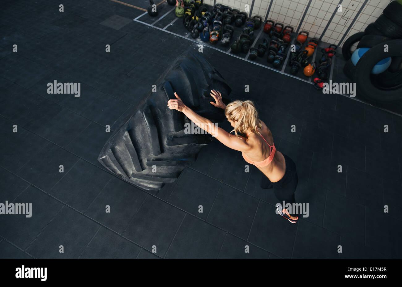 Entraînement à la femme Crossfit gym. Pneu énorme retournement femelle musculaire Photo Stock